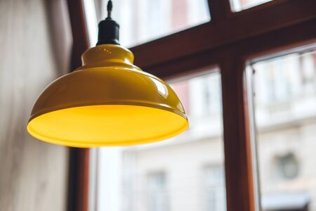 Yellow lamp over wooden table. Lamp in cafe Standard-Bild