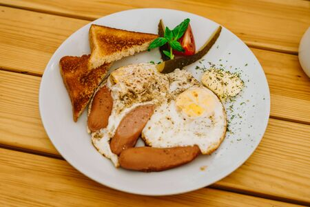 Fried eggs with tomatoes, cucumbers and cheese for breakfast. Scrambled eggs with sausages and tomatoes in a cafe. Comprehensive breakfast with eggs, ham, vegetables and toast