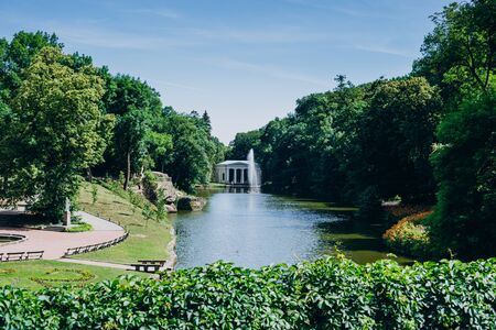 Sofia Park, Ukraine. Dendrological park in summer sunny day. Lake and fountain in a green park.