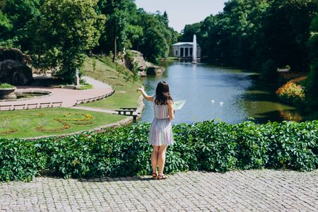 Sofia Park, Ukraine. Young woman with a tourist map walks in a landscaped park. Girl with a tourist map on the background of the lake with a fountain.