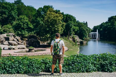 Sofia Park, Ukraine. Man with a backpack in a landscaped park in summer. Man turned his back on the background of the lake with a fountain.