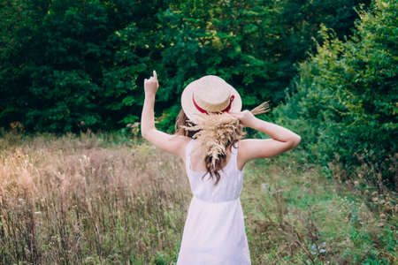 Young woman with curly hair in a hat. Slender girl in a hat with her back turned. Photo of a girl from the back. 스톡 콘텐츠