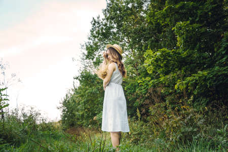 Beautiful girl with curly hair in a hat. Brunette girl walking in a field of flowers. Young woman in summer with a bouquet of dried flowers Reklamní fotografie
