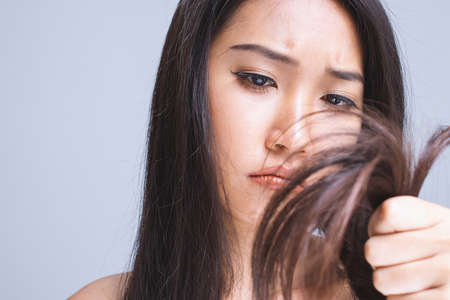 A woman is stressed because of dry hair.