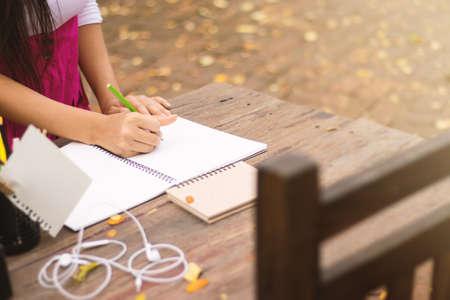 Asian women writing diary in notebook.
