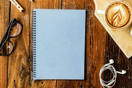 Hot coffee and stationery on the wood table.
