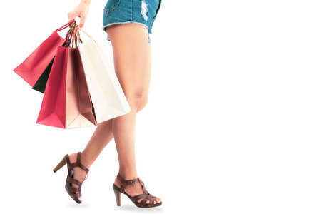 Women are happy with the shopping cart and hand holding paper bags.