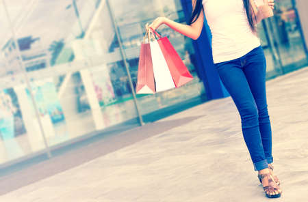 Women are holding a paper bag and shopping at the mall. Stock Photo