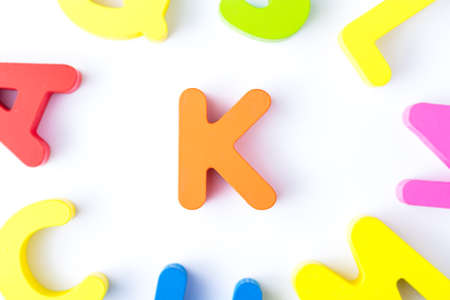 K letters in English made from wood bright colors.