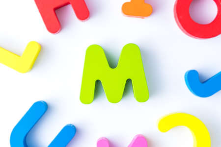 M letters in English made from wood bright colors.