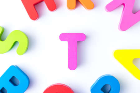 T letters in English made from wood bright colors.