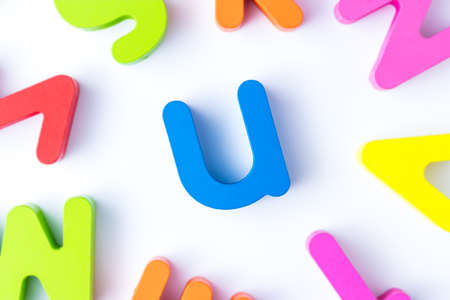 U letters in English made from wood bright colors.