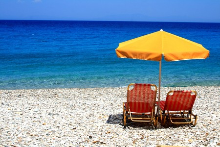 Chairs and an umbrella sit calmly on a beach in Greece while waves lap at the shore.  photo