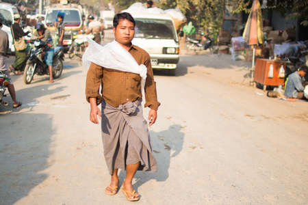 ethnology: Mandalay, Myanmar  - 22  February 2015 . The unidentified man walking in the street with the unique suit.