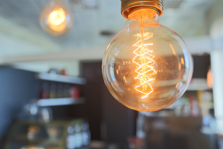 Yellow vintage electric lamp in a cafe Stock Photo