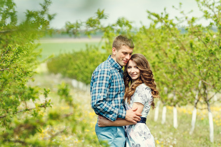 Attractive young happy couple on a spring garden walk in the countryside in front of a tree covered in white blossom