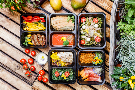 Healthy food and diet concept, restaurant dish delivery. Take away of fitness meal. Weight loss nutrition in foil boxes. Steamed veal with cous and vegetables at wood Reklamní fotografie