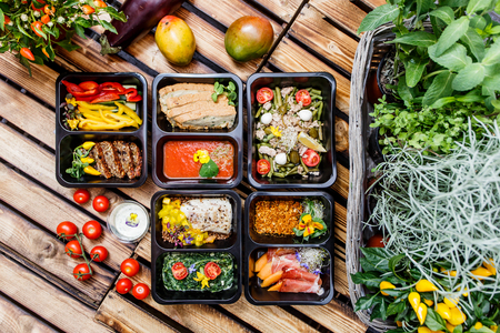 Healthy food and diet concept, restaurant dish delivery. Take away of fitness meal. Weight loss nutrition in foil boxes. Steamed veal with cous and vegetables at wood Standard-Bild