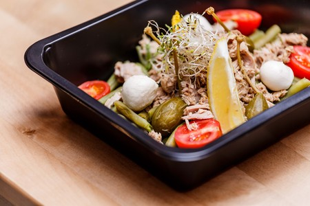 Healthy food and diet concept, restaurant dish delivery. Take away of fitness meal. Weight loss nutrition in foil boxes. Steamed veal with cous and vegetables at wood Stock Photo