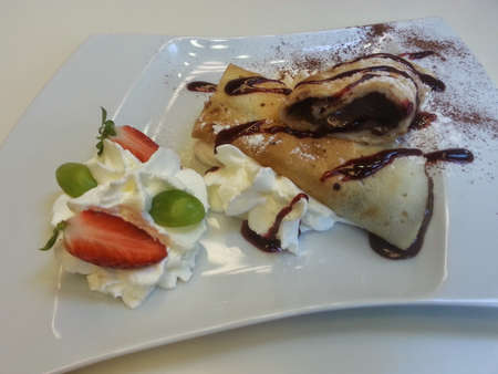 mouth watering: Pancake rolls with chocolate filling and whipped cream on white plate, side view Stock Photo