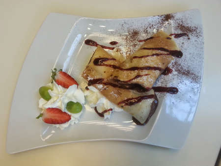 mouth watering: Pancake rolls with chocolate filling and whipped cream on white plate, top view
