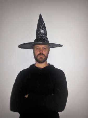 pointy hat: A bearded man in a steeple crowned hat - looking serious