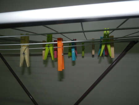 clothespegs: Multicolored clothespegs hanging on a clothes dryer, side view - closeup