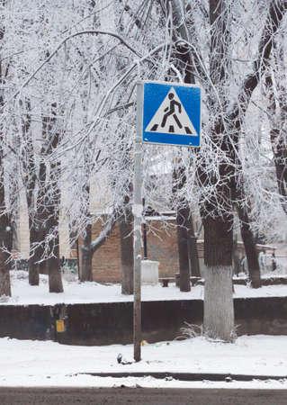 crosswalk: azul se�al de tr�fico peatonal en Kiev bajo la nieve Foto de archivo