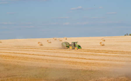 combining: Tractor collecting straw can be used as background