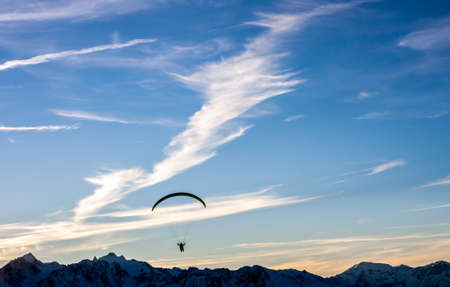 paraglide: Silhouette of paraglide flying over mountains in front of sunset
