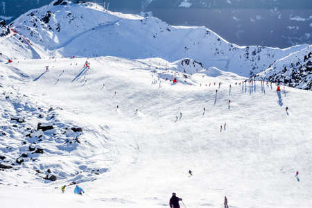piste: View down ski piste with skiers and chairlift on mountains