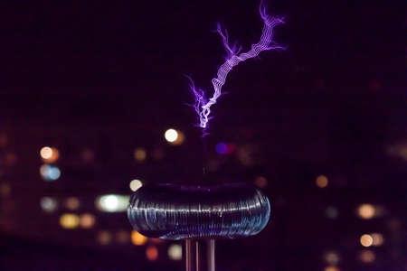 Tesla coil with blue lightning on city lights background
