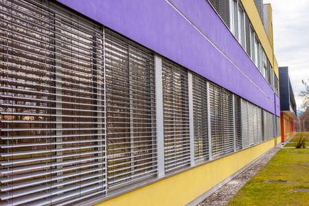 many windows: school wall with many windows and jalousie goes to horizon Stock Photo