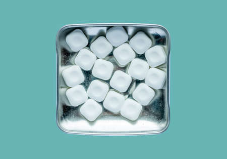 metal box: mint sweets in metal box against the blue background