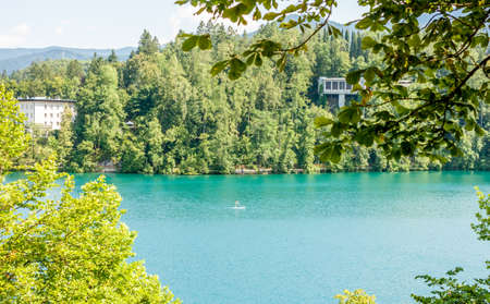 boarder: lake Bled with sup boarder between green trees