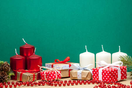 christmas candles and small gifts on green paper background Stock Photo