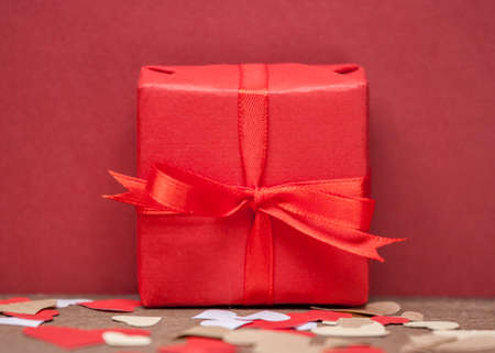 bow knot: red gift box with bow knot and paper hearts Stock Photo