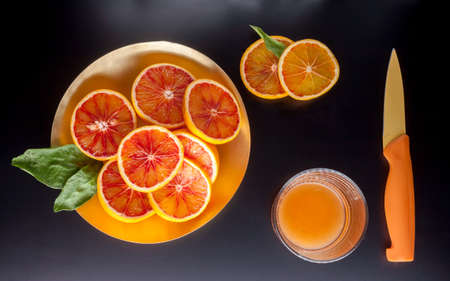 red sicilian oranges glass and knife Stock Photo