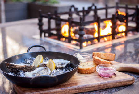 fresh opened oysters fireplace background Stock Photo
