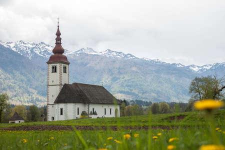dandelion snow: catholic church in field among Alps
