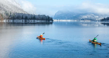 two people kayaking in the winter among mountains