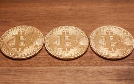 three golden bitcoin coins virtual moneyon wooden background