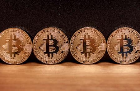 four golden bitcoin coins virtual moneyon wooden background Stock Photo