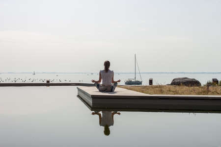 women on seaside meditating in yoga pose