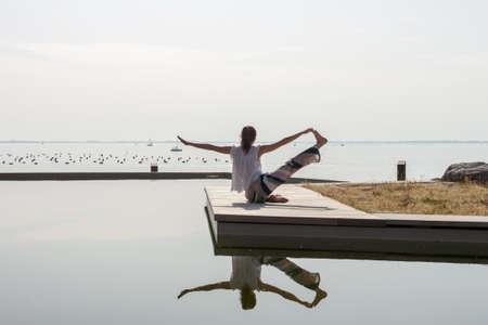 women on seaside meditating in yoga pose