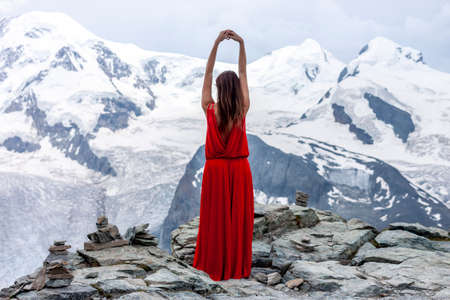 woman in long red dress on background of glacier