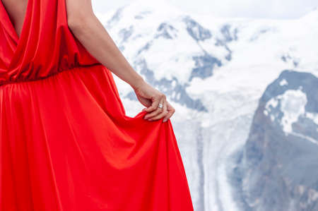 beautiful wooman keeps red long dress ring with gemstone