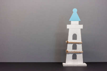 toy lighthouse on blue background with copyspace