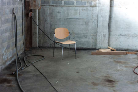 one lonely chair in the corner of abandoned concrete building