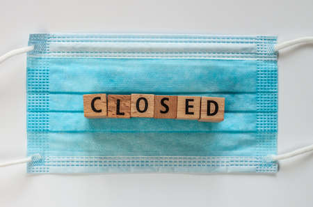 closed word on wooden cubes on blue surgical medical mask